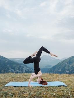 フィットネス自然新鮮な空気の山のためのヨガのエクササイズマットをしている女性。