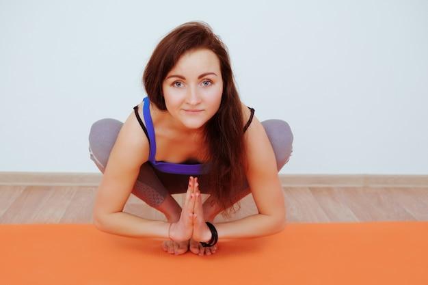 オレンジ色のマットの上でヨガの練習をしている女性、ストレッチ。