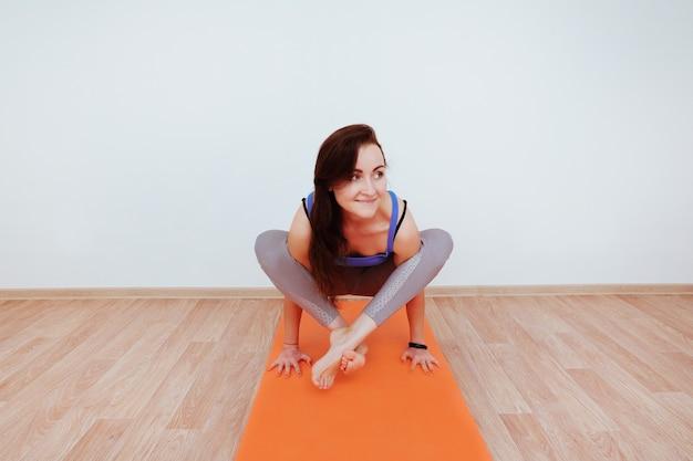 Женщина делает упражнения йоги на оранжевой циновке, растягивая.