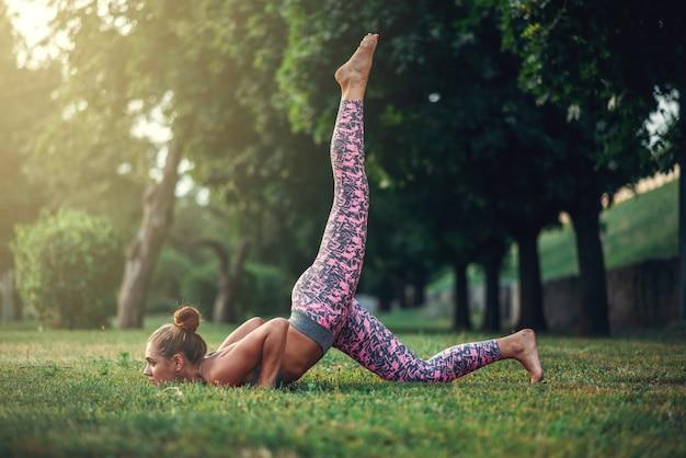 Женщина делает упражнения йоги на траве в летнем парке. утренняя йогическая медитация