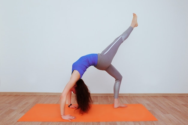 Woman doing yoga exercise on orange mat and stretching