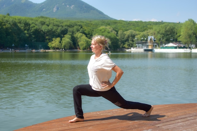 Woman doing yoga exercises in city green park with lake. morning exercise outdoor