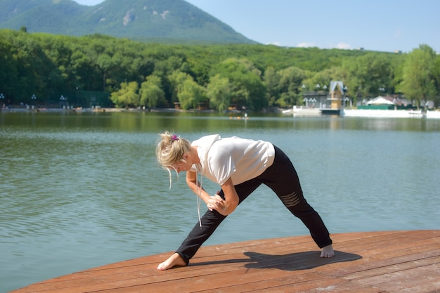 Женщина делает упражнения йоги в городском зеленом парке с озером. утренняя зарядка на открытом воздухе