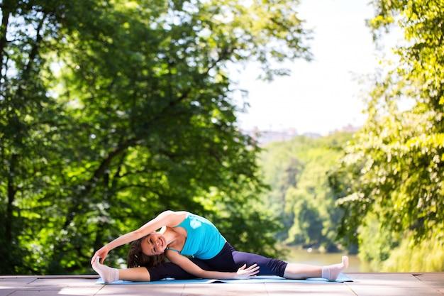 Женщина делает упражнения йоги в парке