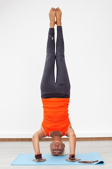young attractive woman in headstand pose studio