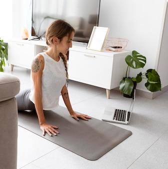 Donna che fa yoga a casa sulla stuoia con il computer portatile