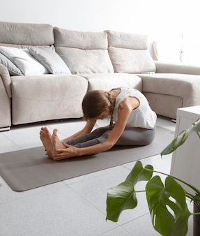 Woman doing yoga at home on mat