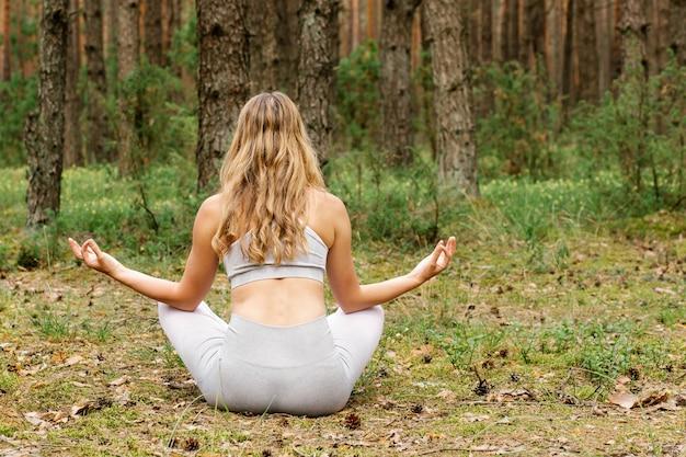 Женщина занимается йогой на природе
