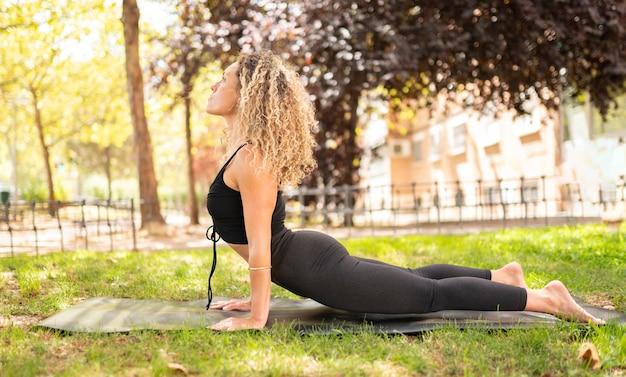 Женщина занимается йогой в парке