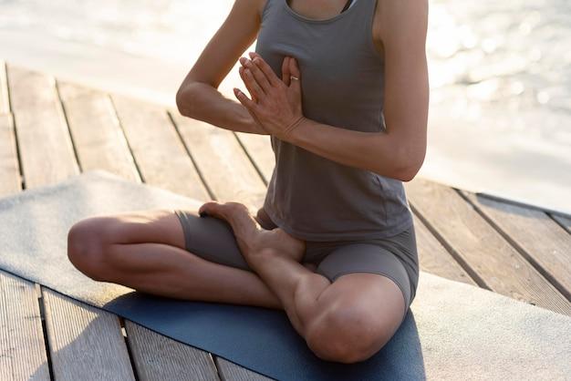 Woman doing yoga on mat near sea