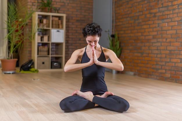 スタジオのナマステで手で完全な蓮華座で瞑想するヨガをしている女性