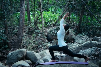 Woman doing yoga meditation pose outdoors at tropical brook in forest