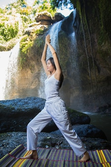 Woman doing yoga and meditation at the waterfall