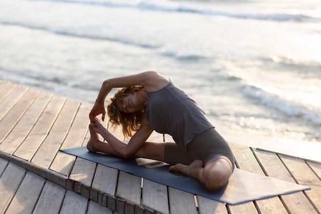 Woman doing yoga near sea