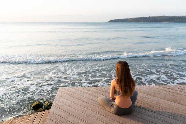 Женщина занимается йогой рядом с морем