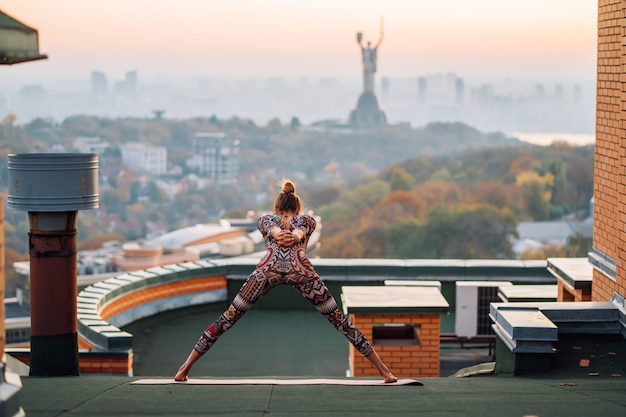 大都会の高層ビルの屋上でヨガをしている女性。