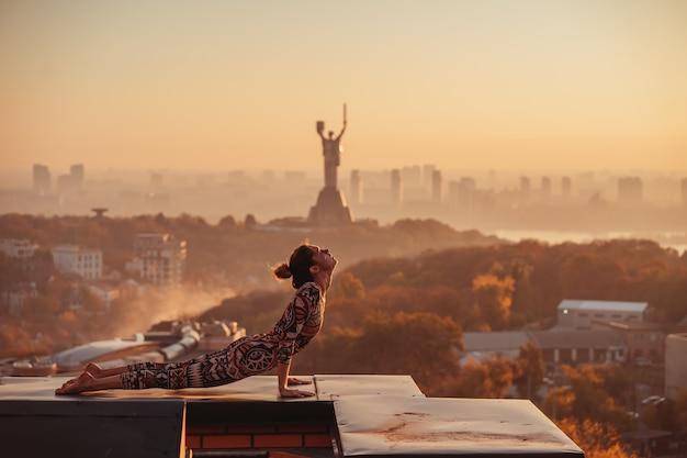 Женщина, занимаясь йогой на крыше небоскреба в большом городе.