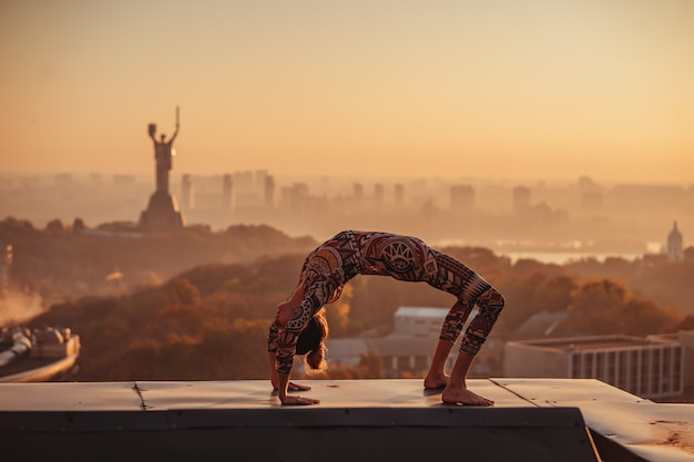 Женщина занимается йогой на крыше небоскреба в большом городе