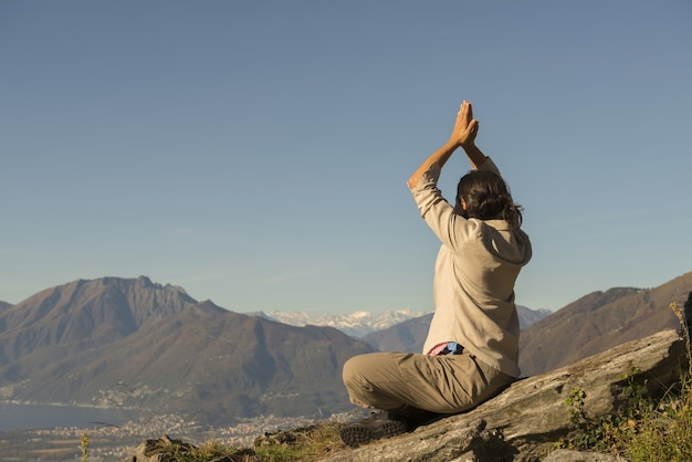 スイスの晴れた日に山の頂上でヨガをしている女性