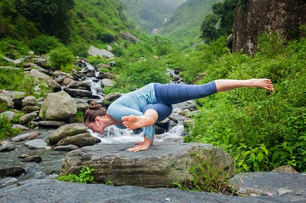 Женщина занимается йогой на тропическом водопаде