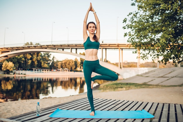 Woman doing yoga outdoors in the summer