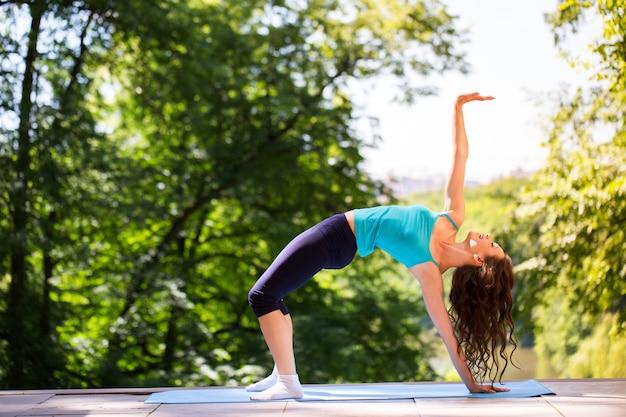 Женщина занимается йогой на открытом воздухе