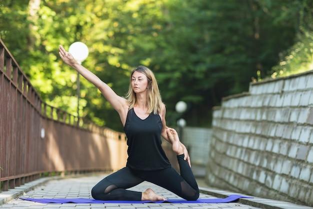 Woman doing yoga in the park doing the exercise eka pada rajakapotasana dove pose