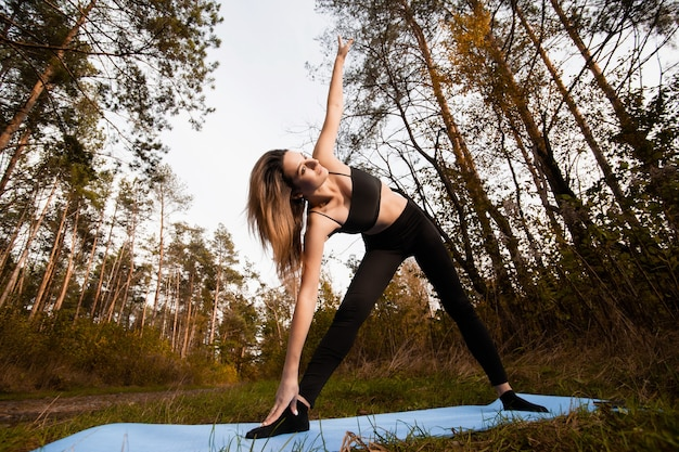 Woman doing yoga or pilates exercise. standing in triangle yoga pose. healthy lifestyle concept. workout outdoors. young woman in black bra and leggins relaxing in yoga asana, practising positions.
