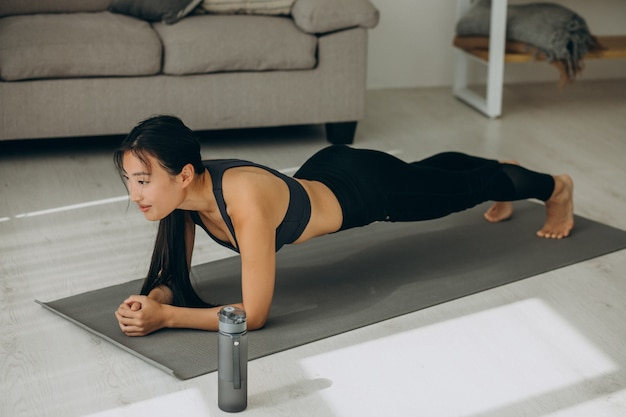 Woman doing yoga plank at home on mat