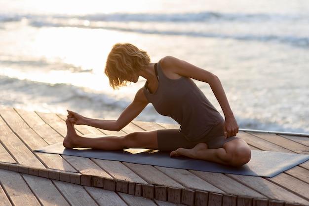 Donna che fa yoga poe vicino al mare