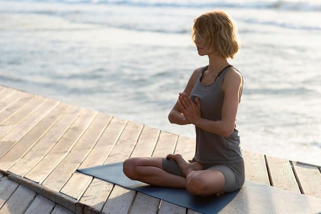 Женщина делает позу йоги на причале