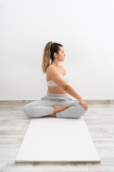 Donna che fa una posa di yoga su una stuoia bianca