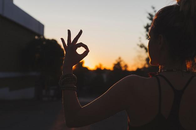 Woman doing yoga on sunset