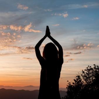 Donna che fa yoga al tramonto