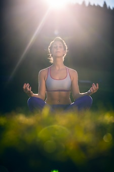 Woman doing yoga in sunset