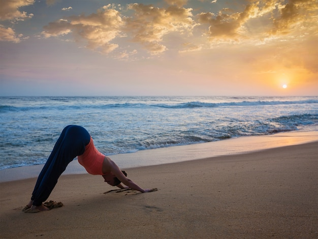 Woman doing yoga surya namaskar oudoors at tropical beach
