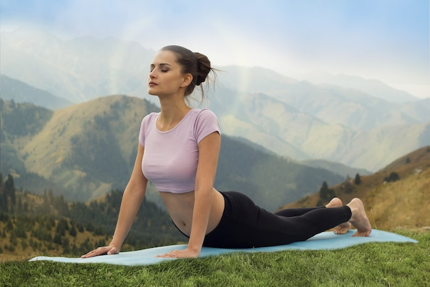 Woman doing yoga surya namaskar sun salutation asana  upward facing dog pose in mountains