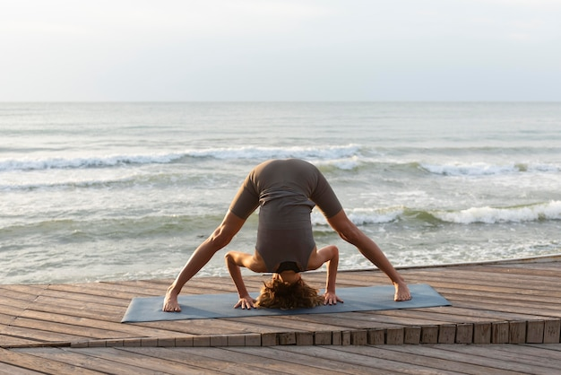 Woman doing yoga towards sea