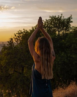 Woman doing yoga while watching the sunset