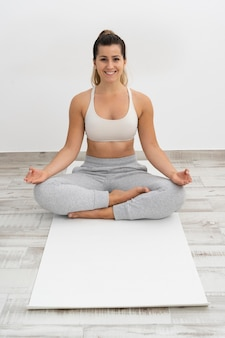Donna che fa yoga su una stuoia bianca