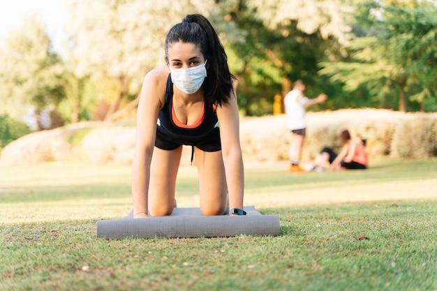 Женщина делает йогу с матрасом в парке носить маску. новая концепция нормальности