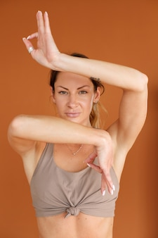 Woman doing yoga with a beige top on an orange background