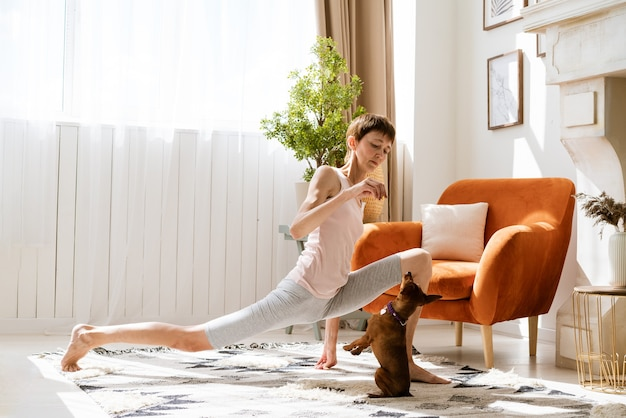 彼女の犬と一緒にヨガをしている女性は、家でヨガを楽しんでリラックスし、犬のコンセプトエクササイズでリラックスしてください...