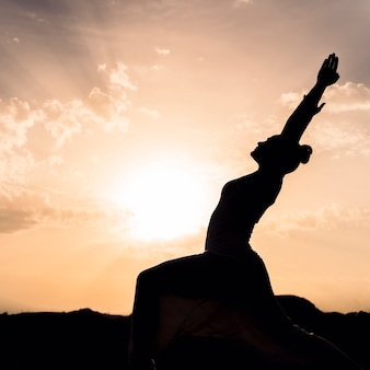 Woman doing yoga with the sunset