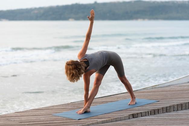 Женщина делает йона на пляже
