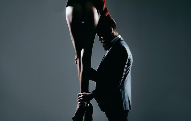 여자는 남자를 지배하고 섹스 게임은 남자에게 복종한다. 전희 성 게임에서 지배. 호화로운 엉덩이, 거대한 엉덩이, 성적인 형태. 사랑과 관계, 지배. 수염을 가진 남자에 신발에 여자의 다리