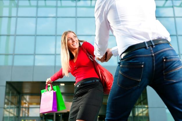 Woman dragging man into shopping mall