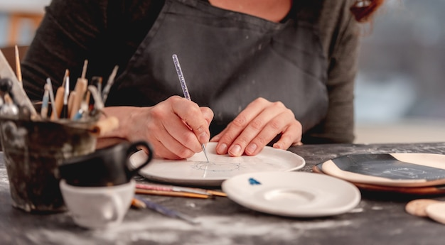 Woman drawing creative pattern on plate made at pottery workshop