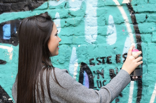 Woman drawing graffiti with spray paint on street wall.