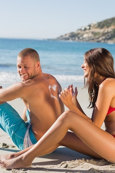 Woman drawing heart pattern with sun cream on her boyfriends back
